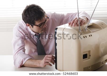 Businessman watching a stylish retro TV - stock photo