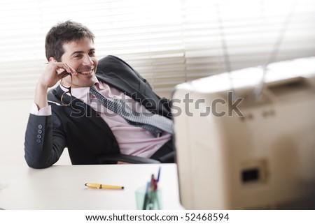 Businessman watching a stylish retro TV, selective focus - stock photo
