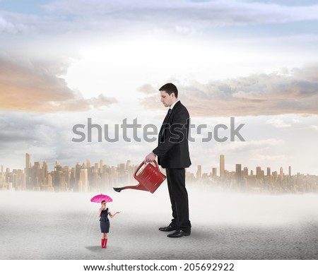 Businessman watering tiny businesswoman against large city on the horizon