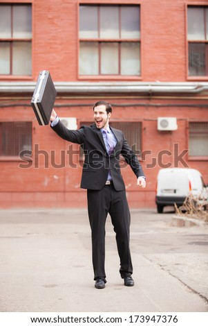 businessman waving his briefcase on the street - stock photo
