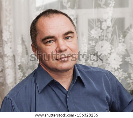 businessman weared blue shirt, mid age man, indoors, looking away , horizontal shot, looking at camera, angle view, toned desaturated image - stock photo