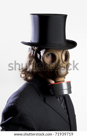 Businessman wearing a gas mask and a top hat - stock photo
