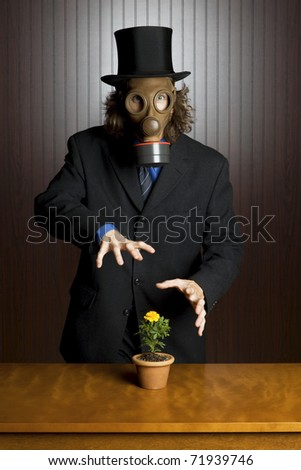 Businessman wearing a gasmask waving his hands over a flower on a table - stock photo