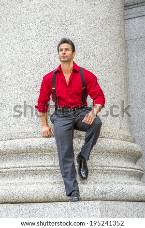 Businessman. Wearing a long sleeve red shirt, trousers with suspenders, leather shoes, bending over, a handsome, strong, middle age businessman is standing against a column, relaxing, thinking.  - stock photo
