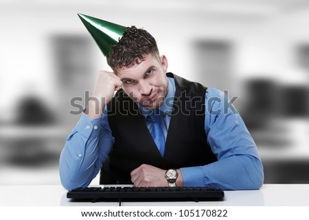 businessman wearing a party hat sitting at his desk - stock photo