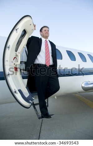 Businessman wearing a suit and tie exiting his corporate jet - stock photo