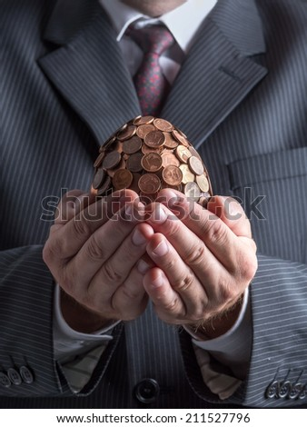 Businessman wearing suit holding one eurocent egg in his hands - stock photo