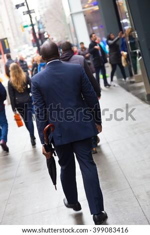 Businessman wearing umbrella, walking crowded sidewalk of Manhattan, New York City, United States of America. - stock photo