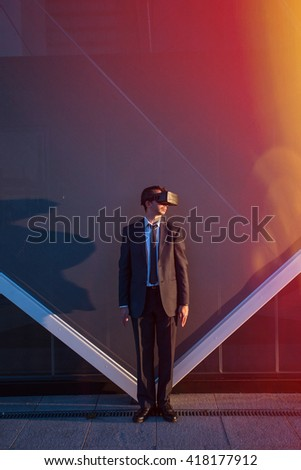 Businessman wearing virtual reality glasses standing outdoors at sunset - stock photo