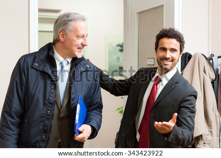 Businessman welcoming another businessman in his office - stock photo