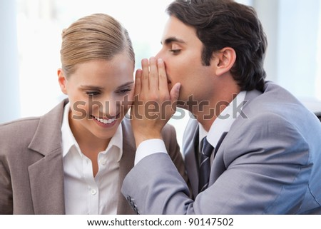 Businessman whispering something to his colleague in a meeting room - stock photo