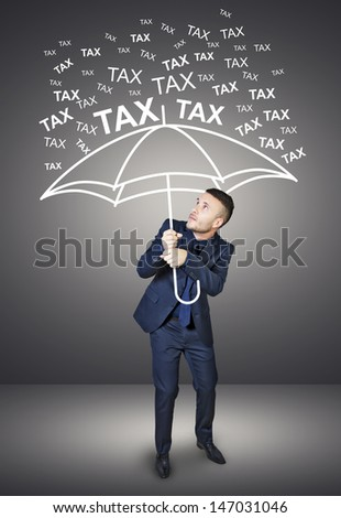 businessman who is protected from taxes - stock photo