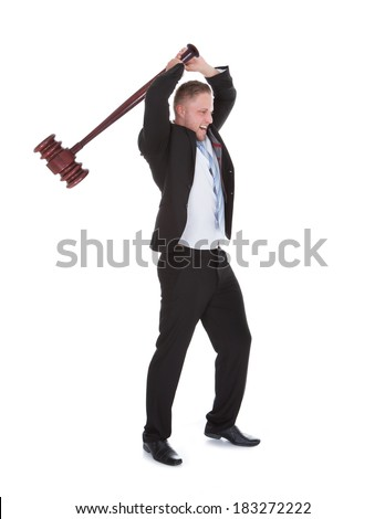 Businessman wielding a big wooden mallet holding it above his head with both hands about to smash it downwards  isolated on white