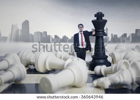 Businessman winning chess game on cityscape background - stock photo