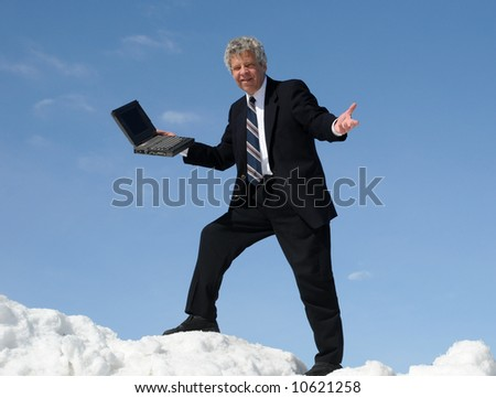 Businessman with a computer on a mountain - stock photo