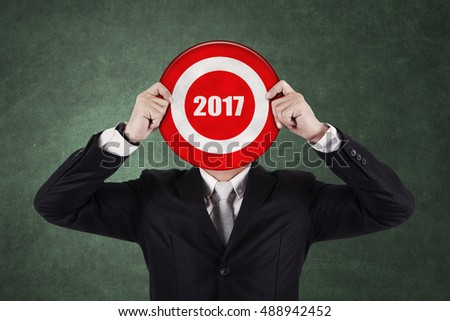 Businessman with a dart in bull's eye with number 2017, Isolated on green background