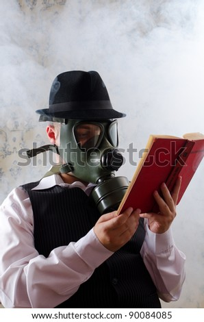Businessman with a gas mask reading a book - stock photo