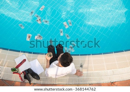 Businessman with a glass of whiskey looking at his money floating in swimming pool