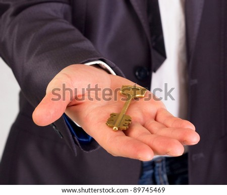 Businessman with a house key in hand isolated on white - stock photo