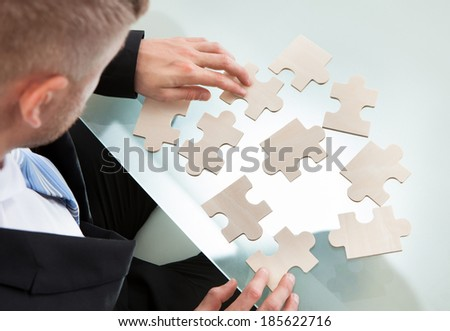 Businessman with a jigsaw puzzle spread out on his desk trying to match the pieces in a concept of problem solving and meeting business challenges  over the shoulder view from above - stock photo