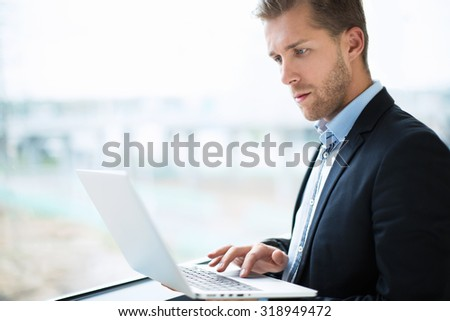 Businessman with a laptop at the airport - stock photo