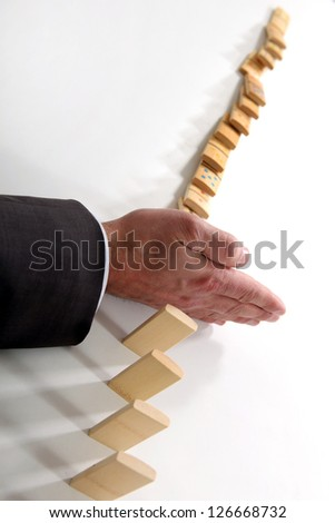 Businessman with a line of dominoes