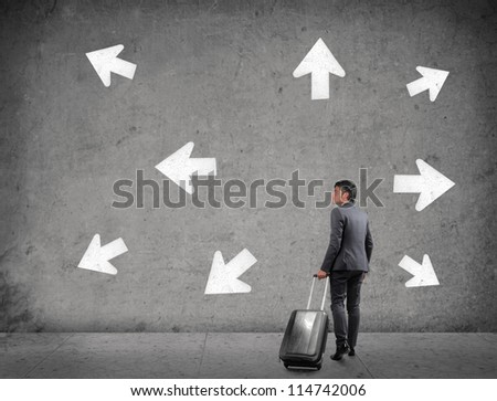 Businessman with a luggage does not know which way to go - stock photo
