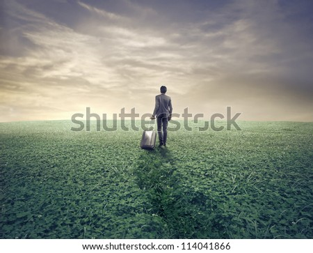 Businessman with a luggage in a wasteland