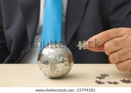 Businessman with a mini puzzle globe - stock photo
