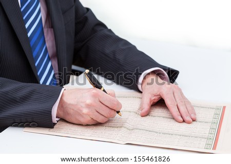 Businessman with a newspaper searching an information