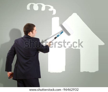 Businessman with a paint brush and picture of house on the wall - stock photo