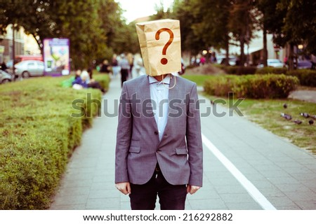 Businessman with a paper bag on head in the street - stock photo