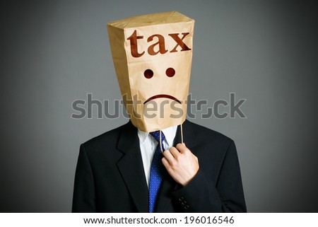 Businessman with a paper bag with tax note on it - stock photo