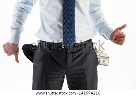 Businessman with a pocket full of money and an empty pocket showing thumbs up and down - stock photo