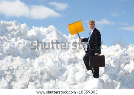 Businessman with a snow shovel and briefcase - stock photo