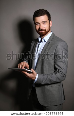 Businessman with a tablet computer. business man using digital tablet computer, leaning against a black wall.  - stock photo