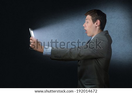 businessman with a tablet computer, the light falls on the face of the screen