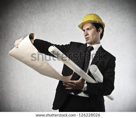Businessman with a yellow helmet checking a design - stock photo