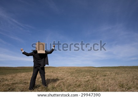 businessman with an box on his head at the field - stock photo