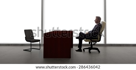 Businessman with an empty chair waiting for a late client.  He looks upset and stressed.  The lonely mood is set by the back light from the large windows.
