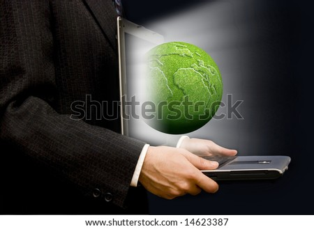 businessman with an open laptop and a green earth globe coming out of the screen - stock photo
