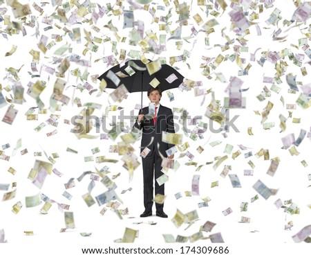 Businessman with an umbrella under the euro rain - stock photo