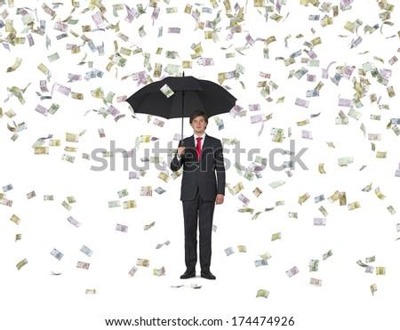 Businessman with an umbrella under the euro rain 2 - stock photo