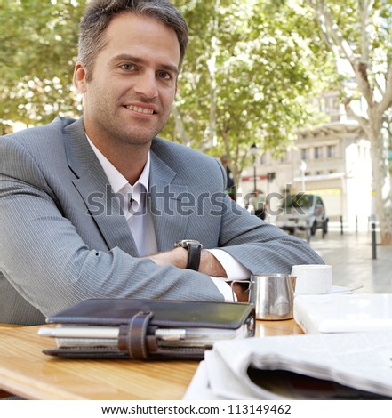 Businessman with arms crossed sitting at a coffee shop table outdoors, smiling. - stock photo