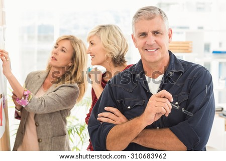 Businessman with arms crossed with his team behind at office - stock photo