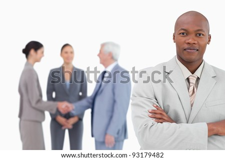 Businessman with arms folded and trading partners behind him against a white background - stock photo
