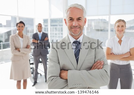Businessman with arms folded standing in front of colleagues behind him - stock photo