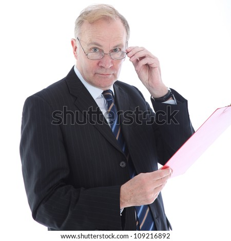 Businessman with assessing look Middle-aged businessman peering over the top of his glasses with an assessing look