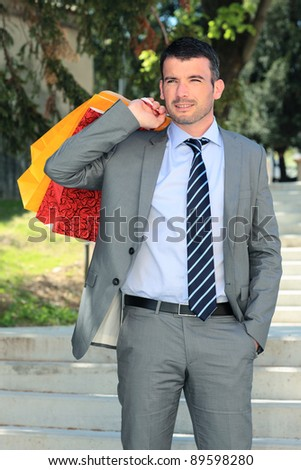 businessman with bags outdoor before christmas - stock photo