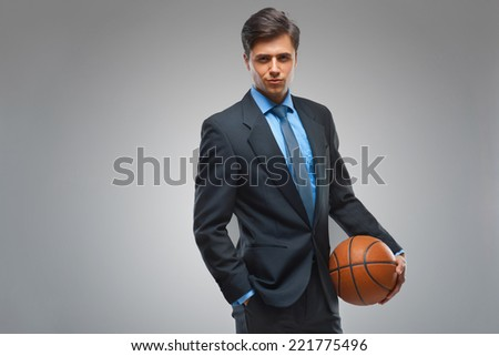 Businessman with ball against gray background - stock photo